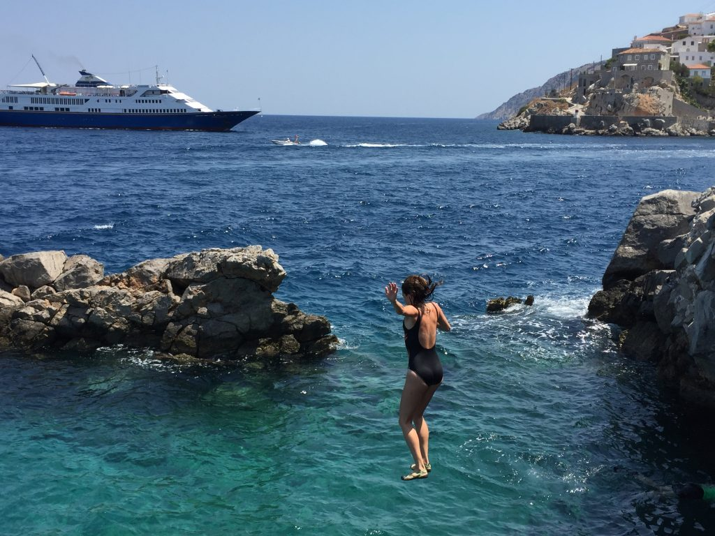 Diving in crystal waters in Hydra, Greece